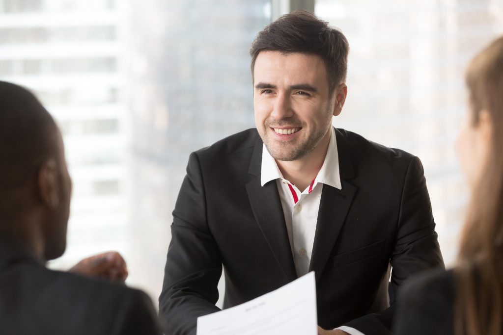 Portrait of confident job candidate talking with multinational interviewers in office, professional specialist communicating with hiring managers. Smiling businessman talking with business partners